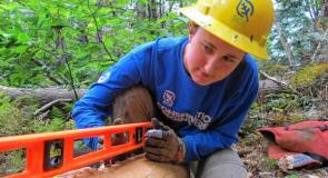 Lizzie Cato of Raleigh, North Carolina, checks the levelness of a log that will be the base for a walking bridge. Photo Credit: Monadnock Ledger-Transcript