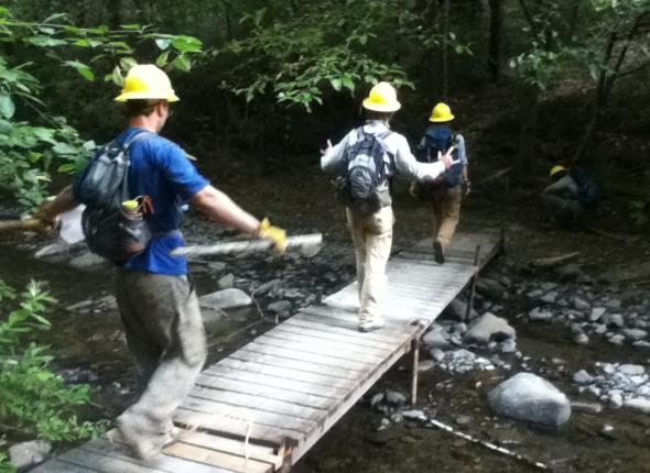 The crew crosses Canoe Creek while heading into the new work site on the River Trail.