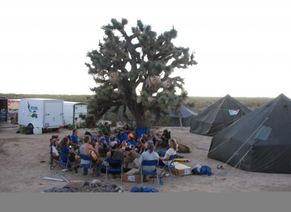 The international restorathletes gather beneath the focal Joshua tree for music and socializing.