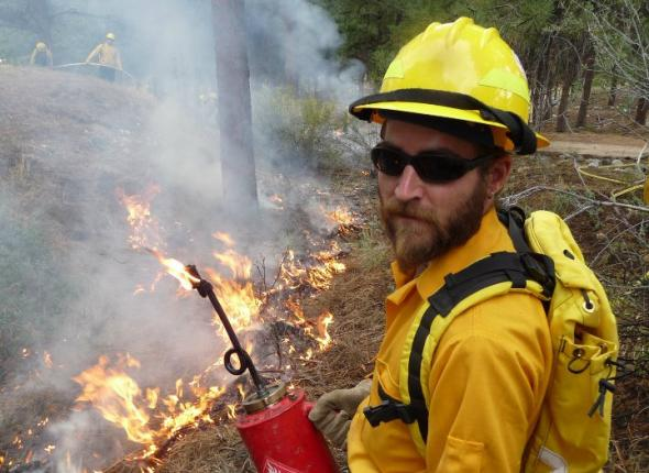 Veteran Fire Corps project leader Bobby Woelz ignites a prescribed line during a controlled burn in the Prescott National Forest
