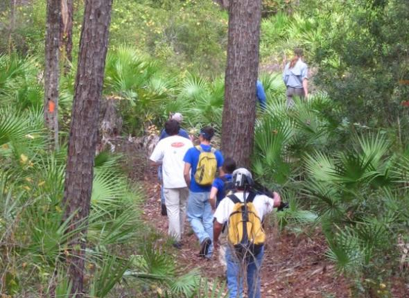 FTA and SCA staff lead the WFSU-TV crew through the forest