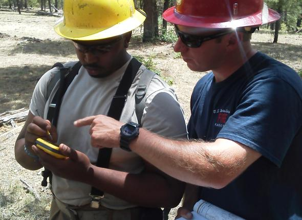 Davon inputs data into a GPS with Forest Service employee Jeff.
