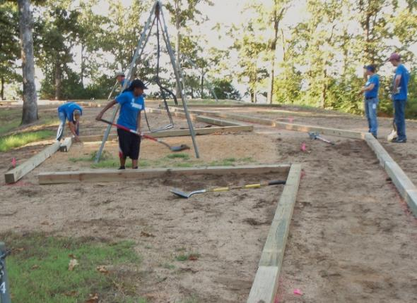 Hickory Ridge playground revitalization at Enid Lake. The team works hard to distribute sand