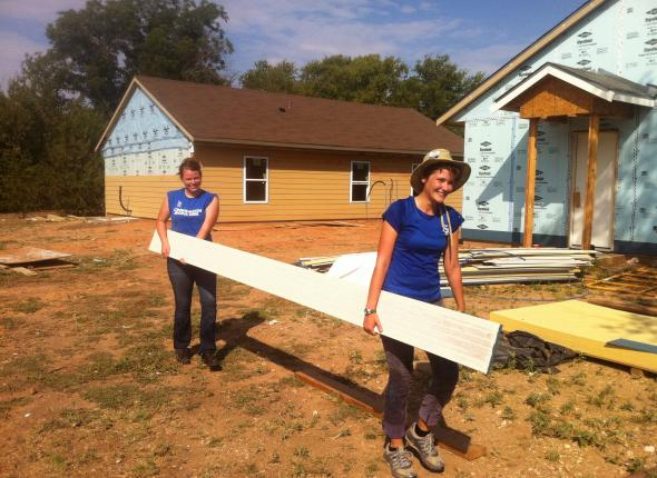 Allison and Kim moving boards at a Habitat for Humanity build