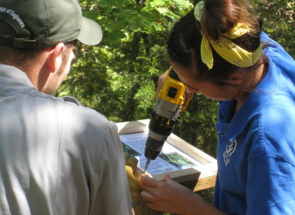 Alaina installing a sign on the Overlook Trail of Tenkiller Ferry Lake.