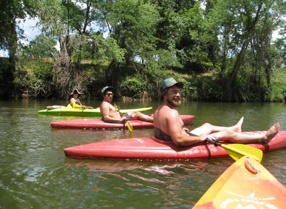 Sophie, Mike, and Clayton kayaking the river.