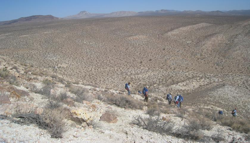 Wilderness crew descends a peak in Grass Valley Wilderness, with Pilot's Knob and the expansive Mojave Desert in the distance.