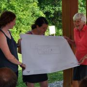 SCA Founder Liz Putnam is presented with plans for the new home of the Hudson Valley Corps at Vassar