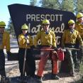 Members of the Veterans Fire Corps pose near the Prescott National Forest sign with their tools.
